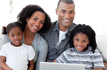 Happy young African-American family using a laptop in the living-room